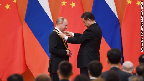 Chinese President Xi Jinping congratulates Russian President Vladimir Putin after presenting him with the Friendship Medal in the Great Hall of the People on June 8, 2018 in Beijing, China.