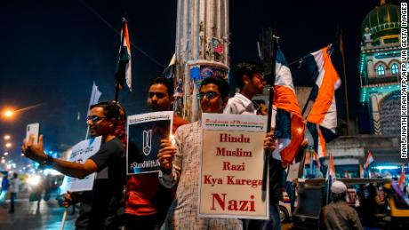 Protesters hold placards and national flags as they stage a candle light vigil condemning Indian Prime Minister Narendra Modi and India's new citizenship law, in Bangalore on January 14, 2020.