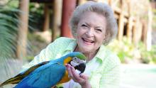 Betty White poses with a parrot.