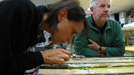 Researchers look at cores of rock drawn from the sea bed.