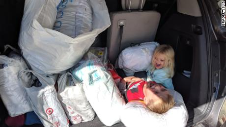 Tyler and his sister, Addison, with a trunk full of bedding donations.