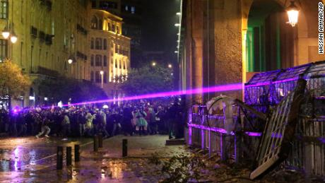Anti-government protesters use lasers as they clash with the riot police.
