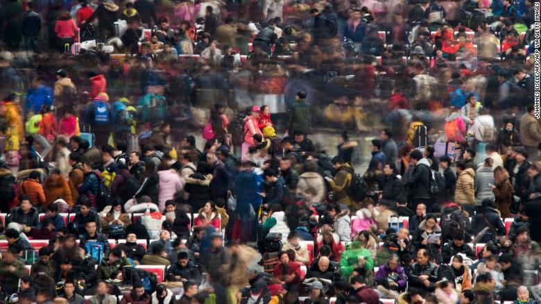 Passengers wait to board their trains as they head to their hometown for the Lunar New Year holiday at a railway station in Shanghai on January 30, 2016.