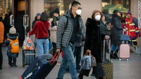 Travelers wear face masks as they walk outside of the Beijing Railway Station in Beijing, Monday, January 20, 2020.