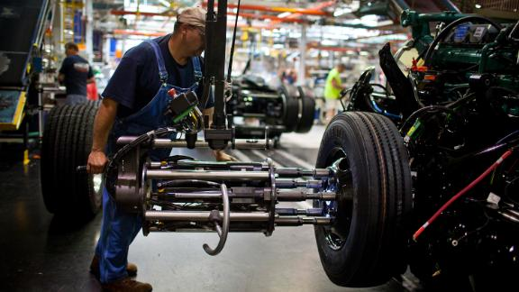 An employee prepares a tire to be mounted onto a truck chassis at the Volvo AG New River Valley Plant in Dublin, Virginia, U.S., on Thursday, May 2, 2013.