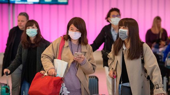 Passengers wear protective masks to protect against the spread of the Coronavirus as they arrive at the Los Angeles International Airport, California, on January 22, 2020. - A new virus that has killed nine people, infected hundreds and has already reached the US could mutate and spread, China warned on January 22, as authorities urged people to steer clear of Wuhan, the city at the heart of the outbreak. (Photo by Mark RALSTON / AFP) (Photo by MARK RALSTON/AFP via Getty Images)