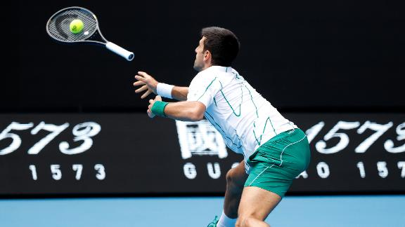 Worth a try? Novak Djokovic launches his racket as he attempts to return a shot against Japan