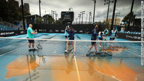 Staff cleaning dirt off the outside courts at Melbourne Park on January 23, 2020 in Melbourne, Australia.