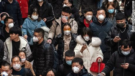 Chinese passengers, almost all wearing protective masks, arrive to board trains at a Beijing railway station on January 23, 2020.