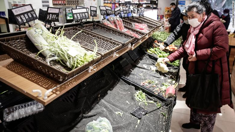 People wear masks while shopping for vegetables in Wuhan on January 23.