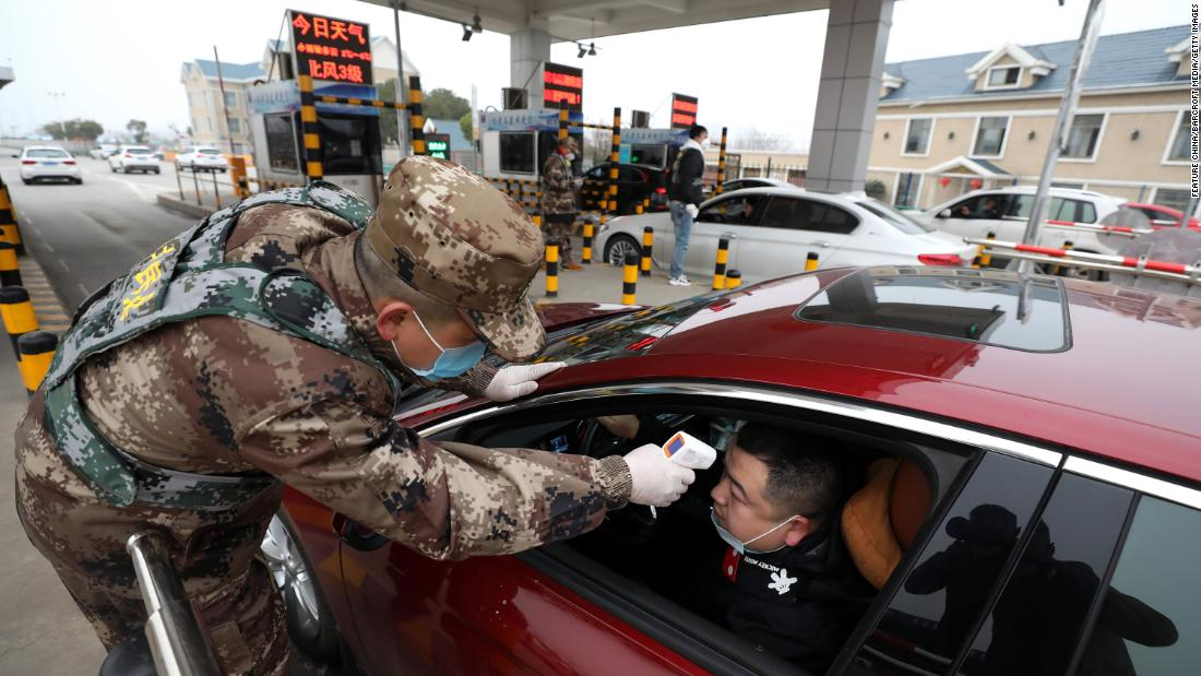A militia member checks the body temperature of a driver in Wuhan on January 23.