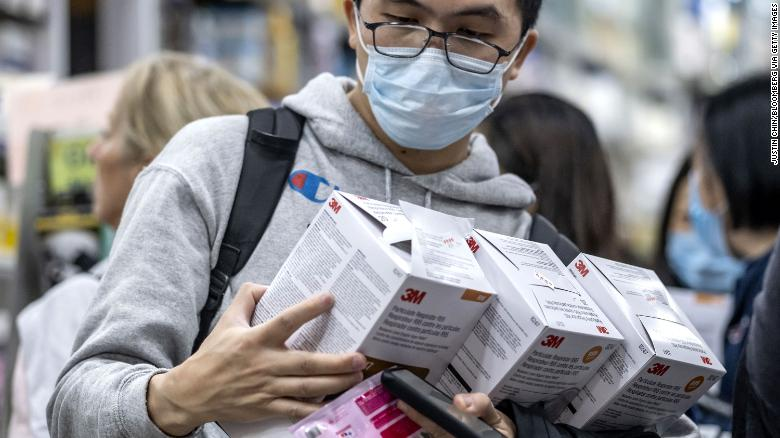 A customer holds boxes of particulate respirators at a pharmacy in Hong Kong on January 23.