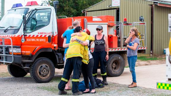 People embrace near the scene of a water tanker plane crash in Cooma, Australia, on Thursday, January 23. Three American crew members died in the crash.
