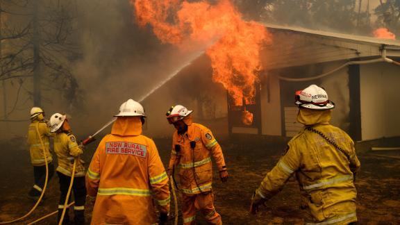 Firefighters battle the Morton Fire as it burns a home near Bundanoon, Australia, on January 23.