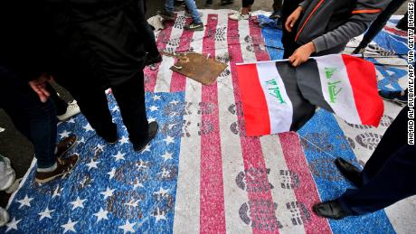 "Protesters step on a makeshift US flag after heeding the call of powerful Shia cleric Muqtada al-Sadr for a ""Million Man March."""