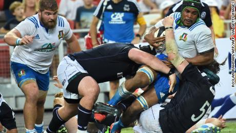 Mbanda is tackled by Scotland's Ben Tools (right).