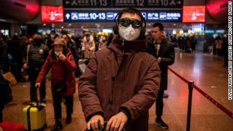 A Chinese man wears a protective mask and goggles before boarding a train at a Beijing railway station on January 23, 2020.