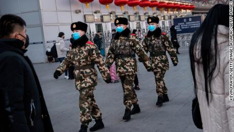 Chinese police officers wear protective masks as they patrol before the annual Spring Festival at a Beijing railway station on January 23, 2020.
