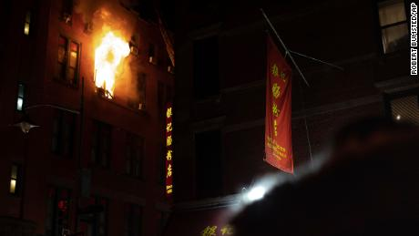 Fire blows out of a window in the Chinatown section of New York, Thursday, Jan. 23, 2020.