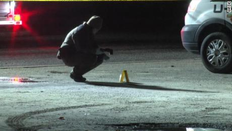 Authorities investigate the scene of the shooting where two young men were killed.