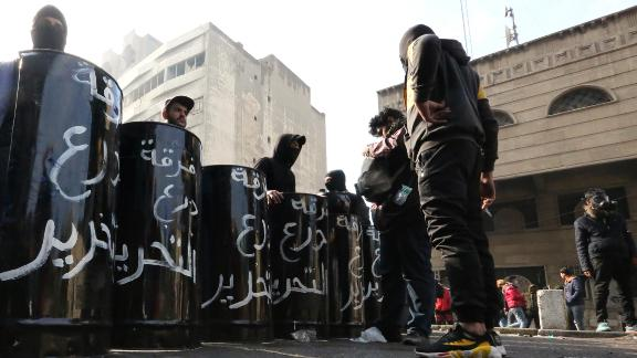 """Iraqi anti-government protesters carry black shields made out of metal drums, on which they had painted the words """"Tahrir Shield Squad."""", as they gather at al-Sinek bridge in the capital Baghdad on January 25, 2020. (Photo by SABAH ARAR/AFP via Getty Images)"""