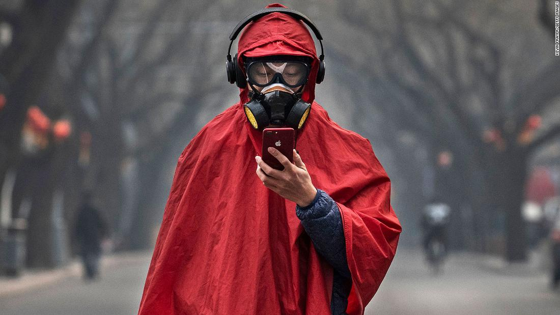 A person wears a protective mask, goggles and coat as he stands in a nearly empty street in Beijing on January 26.