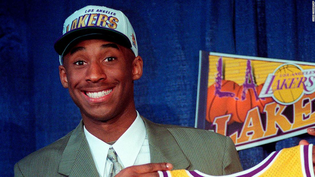 Bryant jokes with the media as he holds his Los Angeles Lakers jersey at a news conference in Inglewood, California, in 1996.