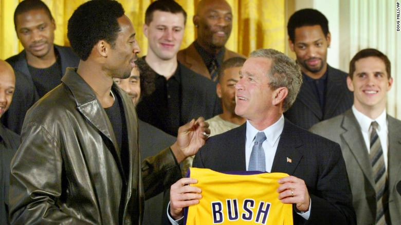 President Bush holds up a Los Angeles Lakers jersey that was given to him by Lakers guard Kobe Bryant, left, during a ceremony for the 2001 NBA World Champions, rear, in the East Room of the White House Monday, Jan. 28, 2002. (AP Photo/Doug Mills)