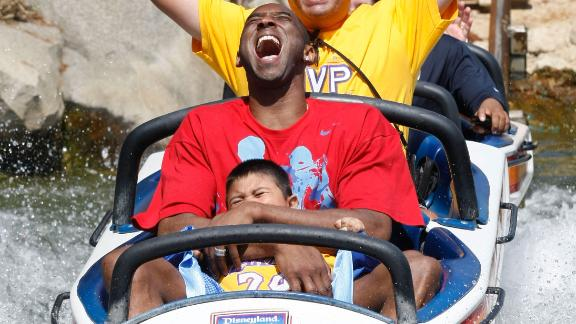 Bryant rides the Matterhorn Bobsleds with Jonathan Guerrero, 4, and his father, David Guerrero of Pomona, California, at Disneyland in Anaheim, California, in 2009. The Guerreros were among thousands of Lakers fans who turned out for a special Disneyland parade honoring the Lakers' 15th World Championship.