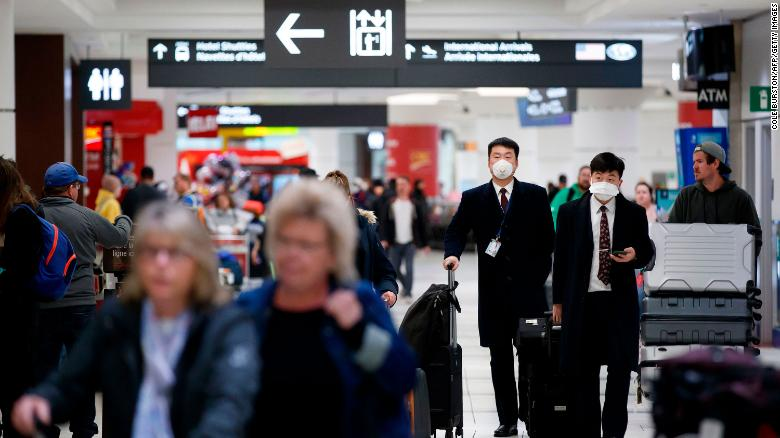 Flight crews wearing masks arrive at the Toronto Pearson Airport in Toronto, Canada, on Sunday, January 26.