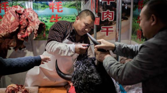This picture taken on January 15, 2020 shows a butcher selling yak meat at a market in Beijing.  (Photo by NICOLAS ASFOURI/AFP via Getty Images)