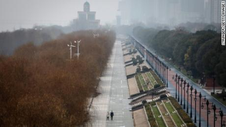 Two residents walk in an empty Jiangtan park in Wuhan, China.