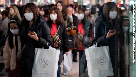 People wearing masks walk through the Ginza shopping district in Tokyo.