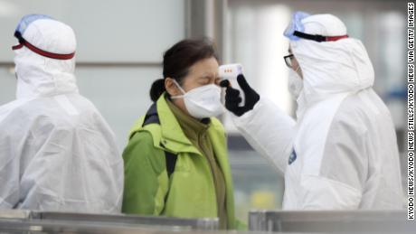 An official checks the temperature of a passenger in front of a train ticket gate at Beijing international airport on January 27, 2020, amid the outbreak of a novel coronavirus.