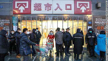 Masked shoppers stop by the entrance to a supermarket in Wuhan.