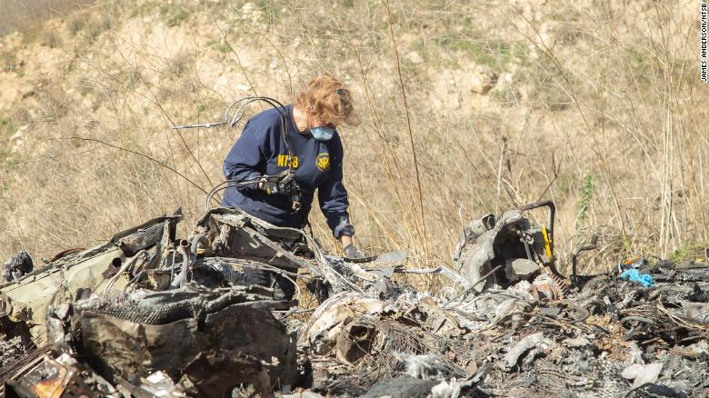 The NTSB's Carol Hogan examines wreckage at the crash site.
