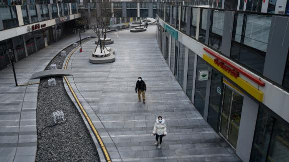 A Chinese couple wear protective masks as they walk in an empty shopping area that would usually be busy during the Chinese New Year and Spring Festival holiday on January 28, 2020 in Beijing, China.