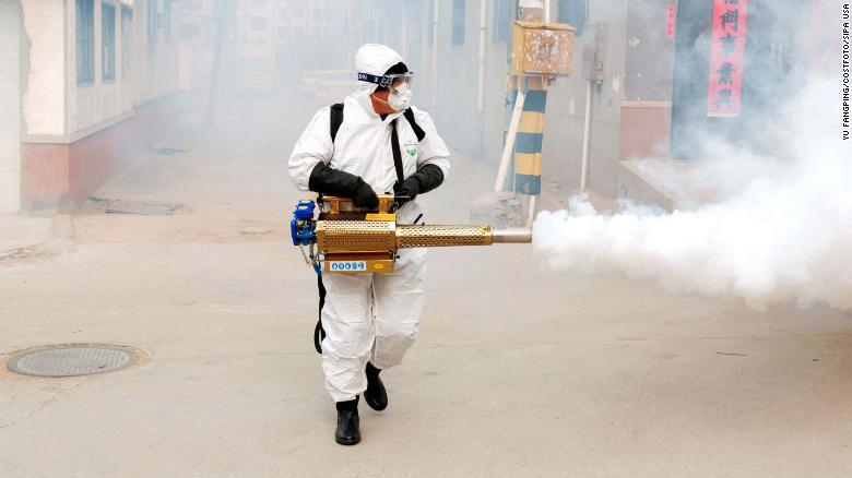 A volunteer wearing protective clothing disinfects a street in Qingdao, China, on Wednesday, January 29.