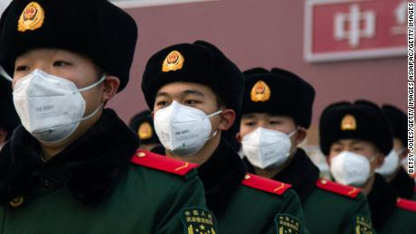 Chinese police officers wearing masks stand in front of the Tiananmen Gate on January 26 in Beijing.