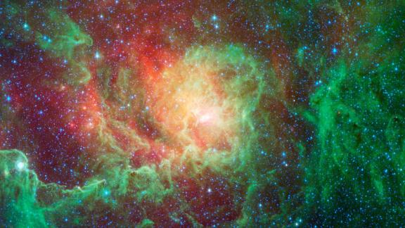 """Swirling dust clouds and bright newborn stars dominate the view in this image of the """"Lagoon nebula"""" from NASA's Spitzer Space Telescope. Also known as Messier 8 and NGC 6523, astronomers estimate it to be between 4000 and 6000 light years away, lying in the general direction of the center of our galaxy in the constellation Sagittarius.The Lagoon nebula was first noted by the astronomer Guillaume Le Gentil in 1747, and a few decades later became the 8th entry in Charles Messier's famous catalog of nebulae. It is of particular interest to stargazers as it is only one of two star-forming nebulae that can be seen with the naked eye from northern latitudes, appearing as a fuzzy grey patch.The glowing """"waters"""" of the Lagoon, as seen in visible light, are really pools of hot gas surrounding the massive, young stars found here. Spitzer's infrared vision looks past the gas to show the dusty basin that it fills. Here we see the central regions of the Lagoon with green showing the glow of carbon-based dust grains, and red highlighting the thermal glow of the hottest dust. The various columns of dust all seem to point inwards towards the central depths of the Lagoon. These structures are being sculpted by the intense glow of giant, young stars found at the nebula's core. Within these clouds of dust and gas, a new generation of stars is forming.This image was made using data from Spitzer's Infrared Array Camera (IRAC). Blue shows infrared light with wavelengths of 3.6 microns, green represents 4.5-micron light and red, 8.0-micron light."""