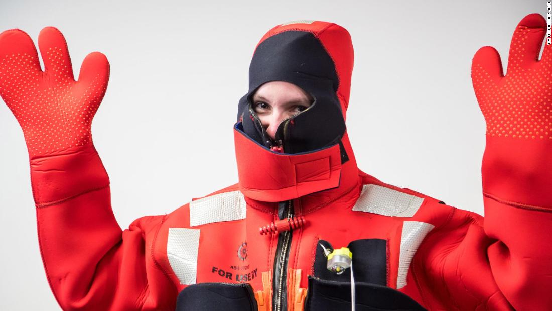 Sibert demonstrating an immersion suit for use in emergency situations at sea.