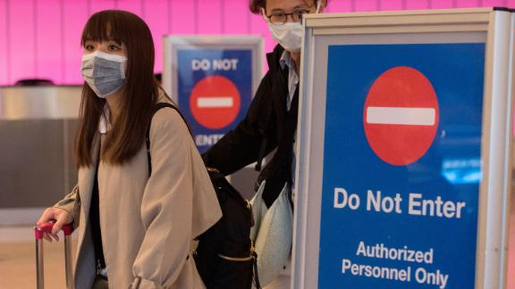 Passengers wear protective masks to protect against the spread of the Coronavirus as they arrive at the Los Angeles International Airport, California, on January 22, 2020. - A new virus that has killed nine people, infected hundreds and has already reached the US could mutate and spread, China warned on January 22, as authorities urged people to steer clear of Wuhan, the city at the heart of the outbreak. ( Mark Ralston / Getty Images)