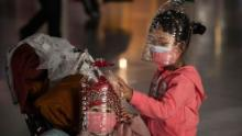 Chinese children wear plastic bottles as makeshift homemade protection and protective masks while waiting to check in to a flight at Beijing Capital Airport on Thursday, January 30 in Beijing, China.