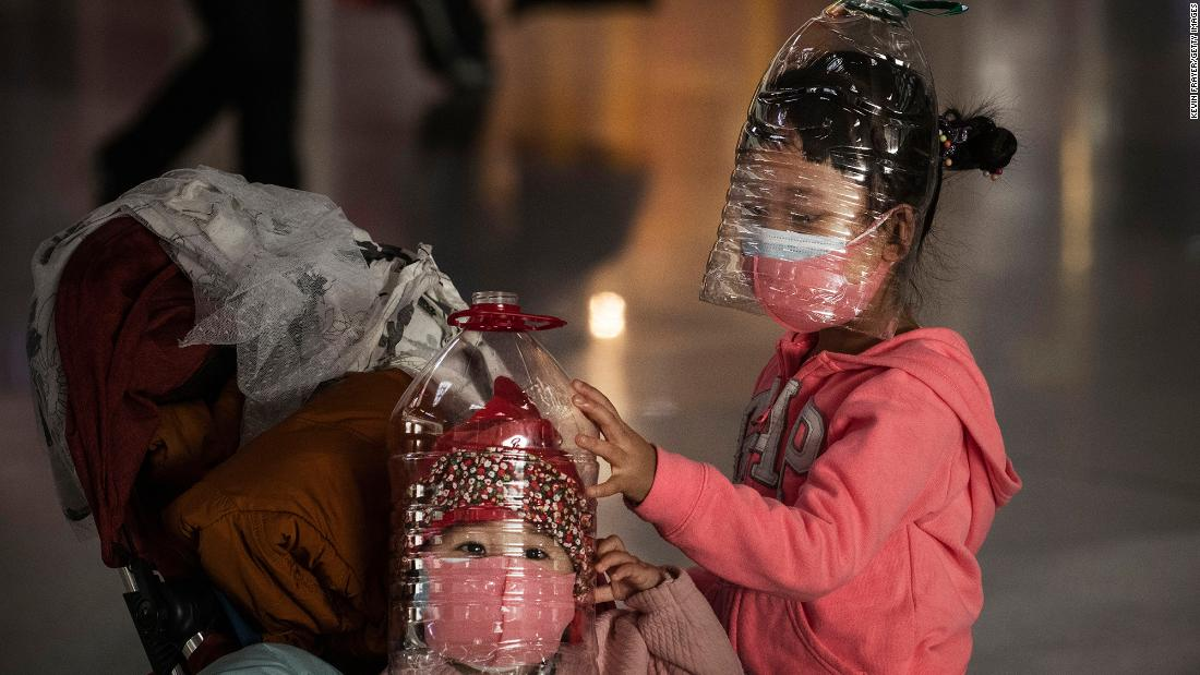 Children wear plastic bottles as makeshift masks while waiting to check in to a flight at the Beijing Capital Airport on January 30.