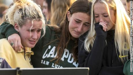 Friends and classmates of Alyssa Altobelli grieve as they look at photos of her during a vigil at Mariners Park in Newport Beach on Thursday.