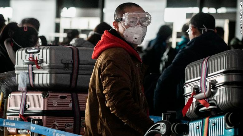 A man wears a protective mask and goggles as he lines up to check in to a flight at Beijing Capital Airport on January 30.