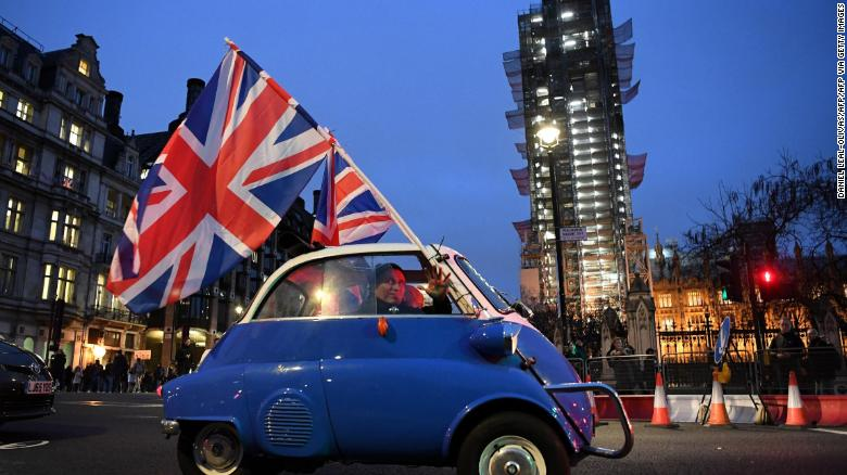 A man waves Union flags from a small car as he drives past Brexit supporters gathering in Parliament Square, near the Houses of Parliament in central London on January 31, 2020 on the day that the UK formally leaves the European Union.