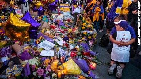 Lakers fans pay their respects at a Staples Center memorial to NBA legend Kobe Bryant, who was killed in a helicopter accident in Los Angeles, California.