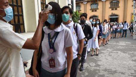 Students wearing protective face masks have their temperatures taken while entering their college campus in Manila.