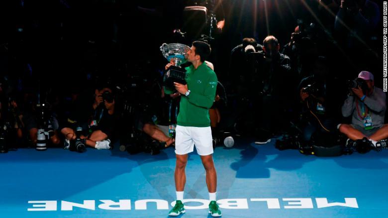Новак Джокович целует трофей после победы на Открытом чемпионате Австралии.